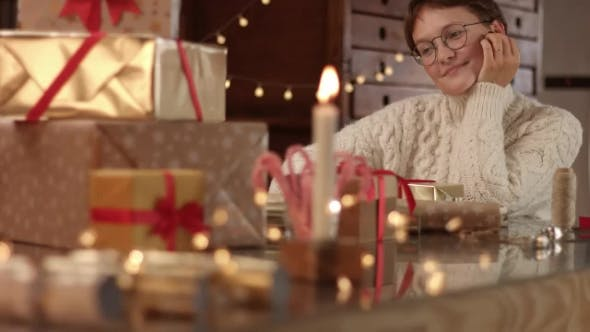 Thumbnail for Cute Young Woman in Cable Sweater Wrapping Presents