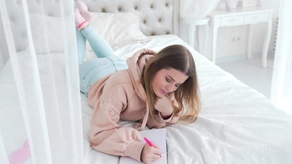 Thumbnail for Happy Smiling Woman Lies on the Bed and Writes Her Impressions and Thoughts in Her Diary, Girl in