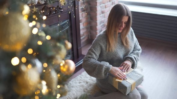 Thumbnail for Pretty Woman in Grey Sweater Decorates Presents Box and Puts It Under the Christmas Tree, Shiny