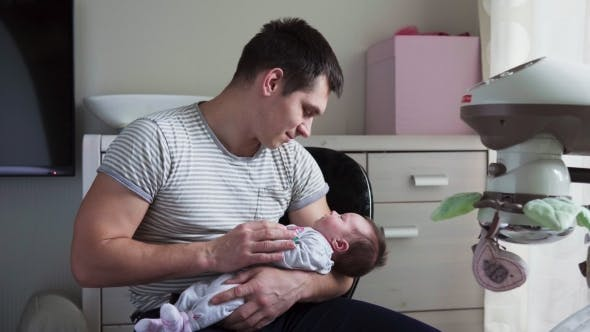 Thumbnail for Father Holds Newborn Baby in Arms
