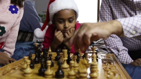 Thumbnail for Smiling Girl in Santa Hat Watching Chess Game