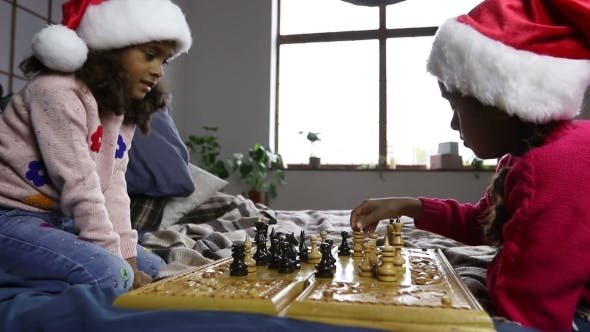 Thumbnail for Two Young Chess Players in Santa Hats Indoors
