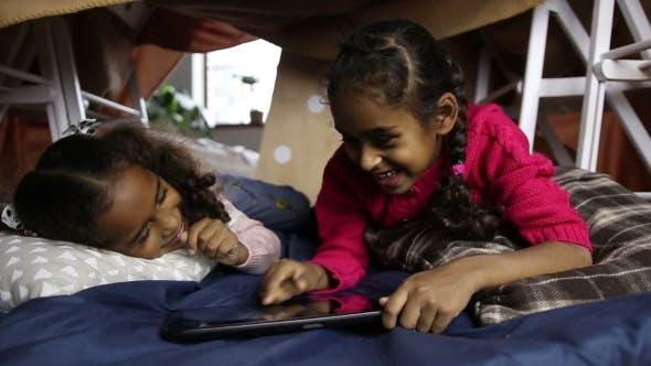 Thumbnail for Zwei kleine Schwestern spielen mit Tablet PC zu Hause