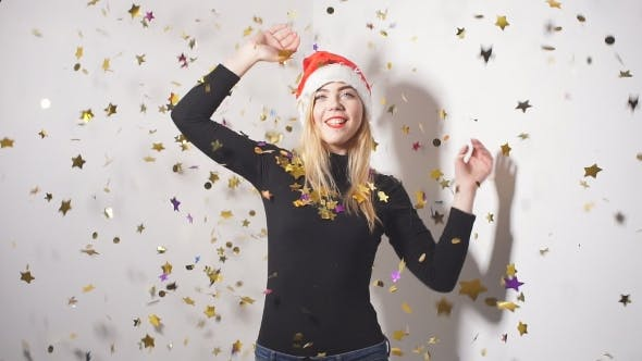 Thumbnail for Cheerful Happy Girl in Red Hat Santa Claus Having Fun While Dancing Under Confetti Fireworks.