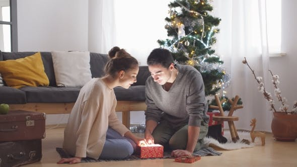 Thumbnail for Young Couple Opens a Christmas Gift.