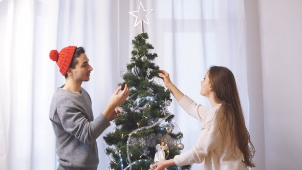 Thumbnail for Young Couple Decorates a Christmas Tree.