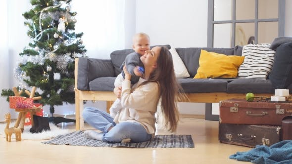 Thumbnail for Young Happy Joyful Family. Mother and Baby Boy Son Having Fun Near Christmas and New Year Tree