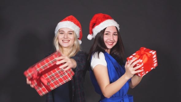 Thumbnail for Two Attractive Girls with Christmas Gifts in Hands Laughing and Dancing Looking at Camera.