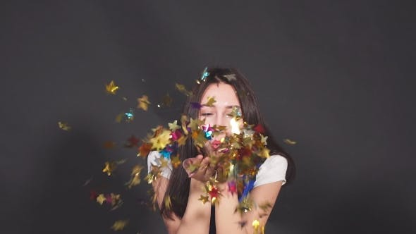 Thumbnail for Young Attractive Woman Blowing Golden Confetti From Hands.