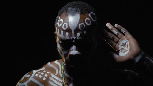 Bearded Papuan in White Ritual Patterns Looking for Someone in the Dark