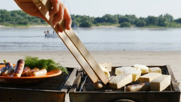 Barbecue - Grilling Sausages and Tofu on a River Beach