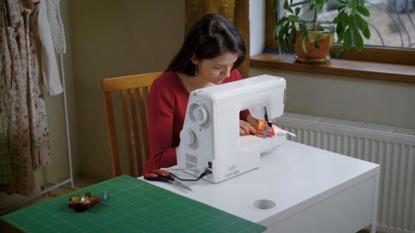 Thumbnail for A Young Woman Is Working Behind an Electric Sewing Machine in the Atelier, a Lady Is Making a Stitch