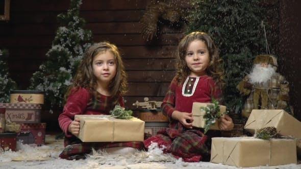 Thumbnail for Kleine Schwestern in Kleidern sitzen mit Geschenken im Weihnachtszimmer und der Schnee fällt auf