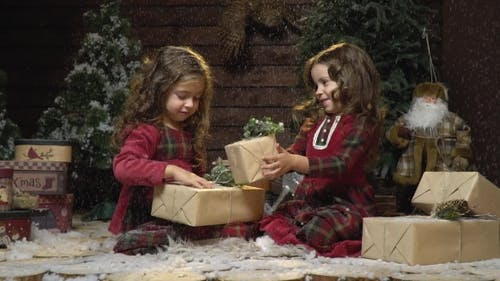 Lovely Sisters in Red Dresses Are Sitting with Presents in a Room with Christmas Decorations and