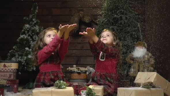 Thumbnail for Twin Girls in Dresses Are Sitting in a Room with Christmas Decorations and Catching Snow,