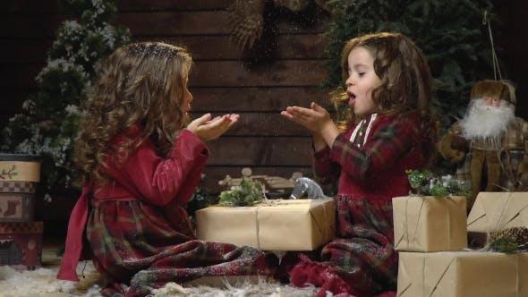 Thumbnail for Schwestern in Kleidern sitzen unter Spielzeug und Geschenke in einem Raum mit Silvesterkleidern und Spaß haben Blasen