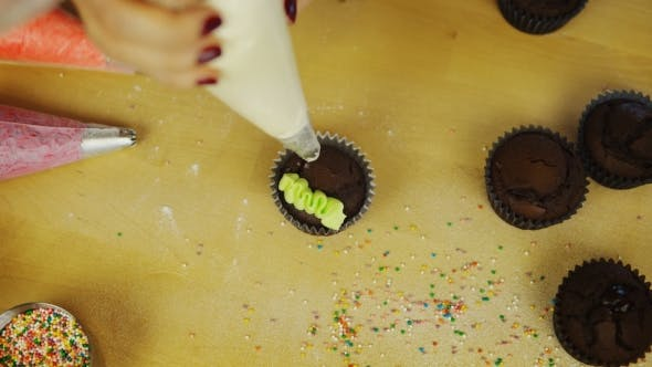 Thumbnail for Young Woman Hands Decorating the Chocolate Cupcakes with Colored Cream. Female Using the