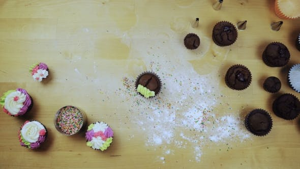 Thumbnail for Top View of Female Hands Decorating the Chocolate Cupcakes. Young Woman Using the Pastry Bag for