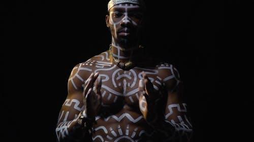Ein schwarzer Mann in weißen Mustern und ein ritueller Hut beten auf einem schwarzen Hintergrund,
