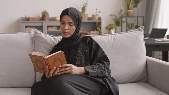 Muslim Woman Reading Koran at Home