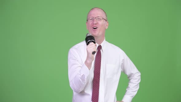 Thumbnail for Happy Mature Bald Businessman Singing on the Microphone