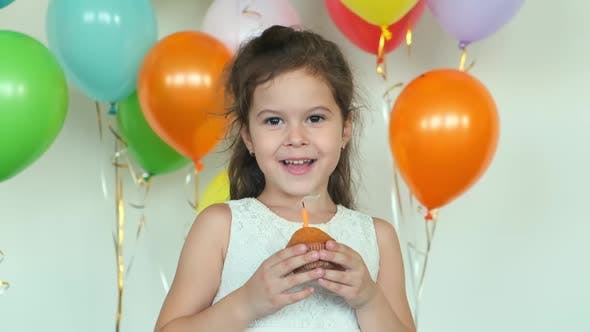 Thumbnail for Girl in Dress Smiles Holding Cupcake with Burning Candle