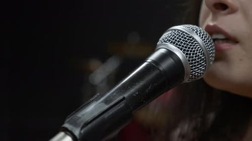 Woman singer is emotionally singing song into microphone, close up.
