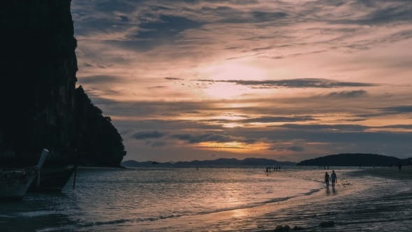 Jung Couple Walking on the Beach. Sunset. Thailand.