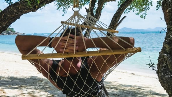 Thumbnail for Man Swinging Relaxed in a Hammock on the Beach in Front of the Beautiful Blue Ocean and Other Island