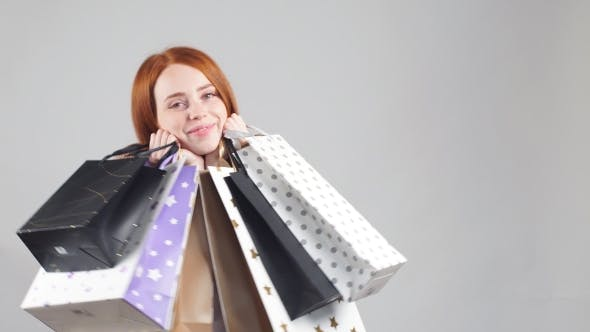 Thumbnail for Beautiful Smiling Redhead Girl with a Lot of Shopping Bags.