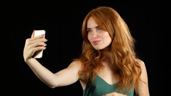 Thumbnail for Girl Makes Selfie on Her Smartphone. Black Background