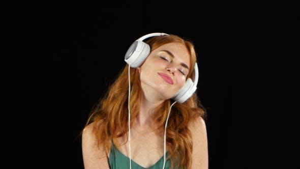 Thumbnail for Girl Listens To Her Favorite Music Through Headphones. Black Background