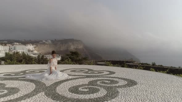 Thumbnail for Aerial view of woman with wedding dress, Santorini island, Greece.