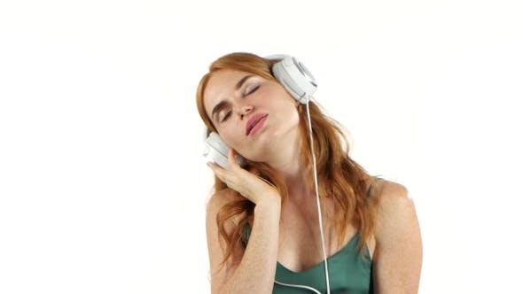 Thumbnail for Girl Listens To Her Favorite Music Through Headphones. White Background
