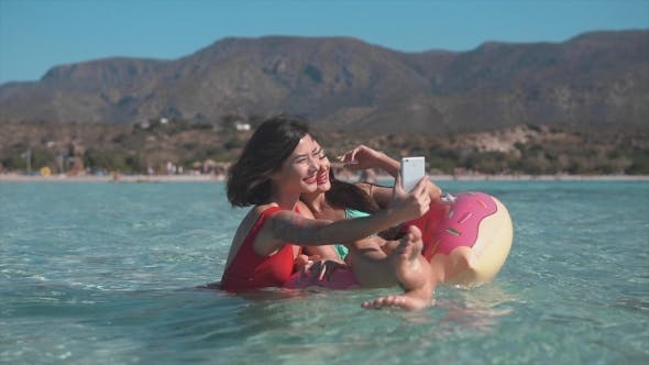 Thumbnail for Two Young Ladies on Inflatable Ring Making Selfie