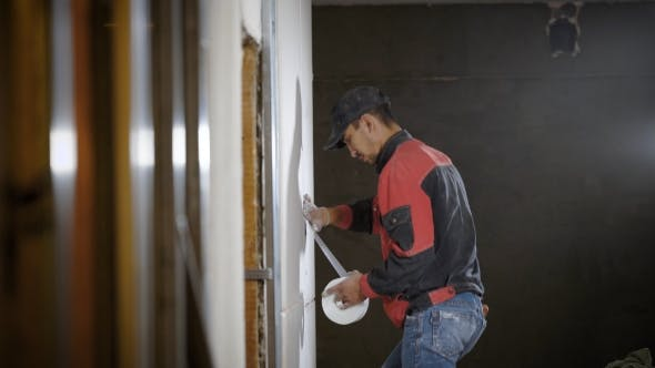 Thumbnail for Worker Is Making Marks on a Plasterboard, Fixed on a Wall, Sticking Tape, During Repair of Apartment