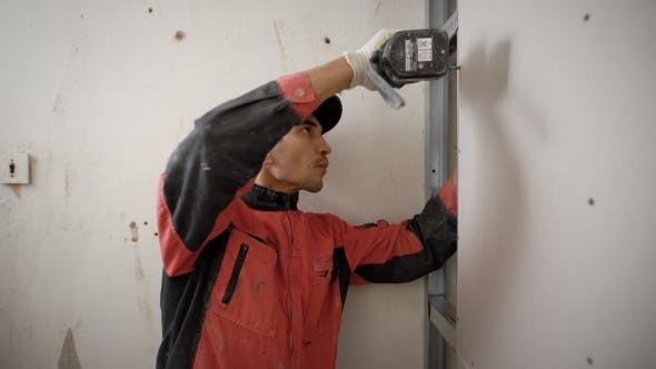 Thumbnail for Installer of Plasterboard Construction Is Twisting Screws in a Wall, Using Cordless Screwdriver