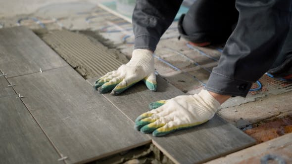 Thumbnail for Tiler Is Installing Ceramic Floor Tiles Above Cement and Electric Floor Heating, Aligning