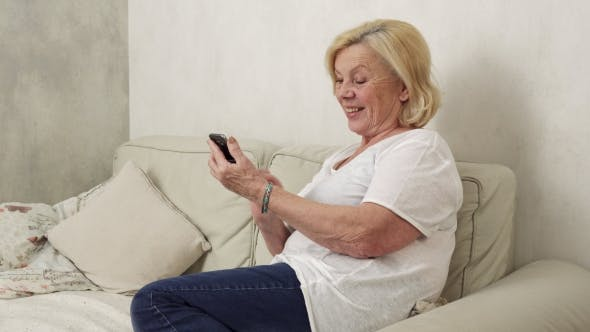 Thumbnail for Happy Elderly Woman Uses a Smartphone
