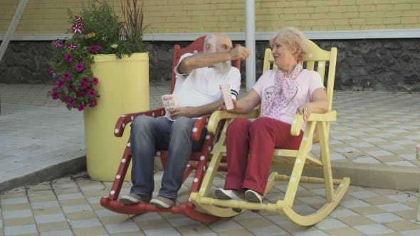 Thumbnail for Old People Swings in Rocking Chair and Eats Popcorn