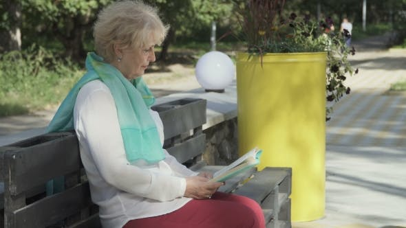 Thumbnail for Senior Woman Reads Book in Park