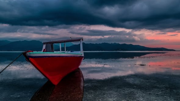 Cover Image for Red Fishing Boat on the Background Dramatic Sunset in the Gili Islands, Indonesia
