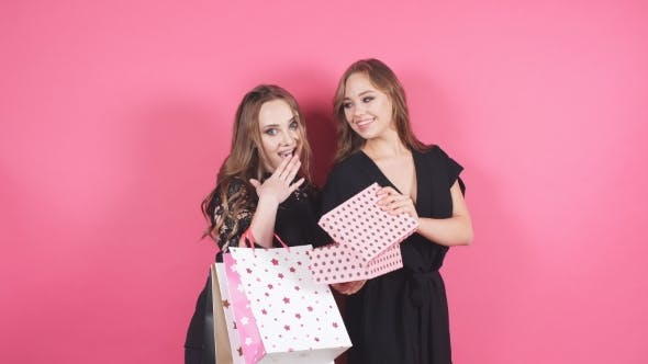 Cover Image for Two Smiling Girls Give Gifts To Each Other on an Isolated Background.