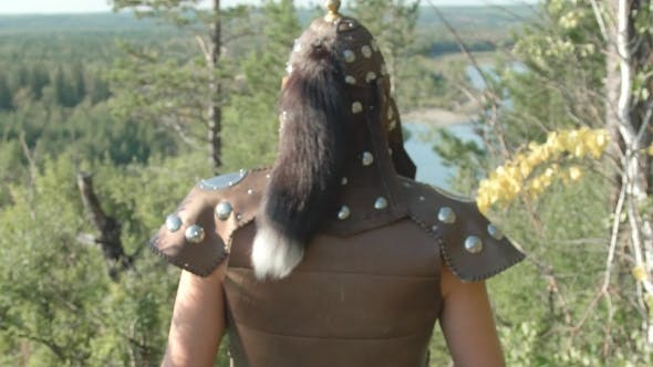 Thumbnail for Rear View of Warrior in Old Armor with Fur That Goes Forest in Summer.