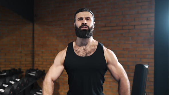 Thumbnail for Strong Man Is Pumping Muscles at the Gym, Power Exercises with Dumbbells, Athlete at Fitness Club