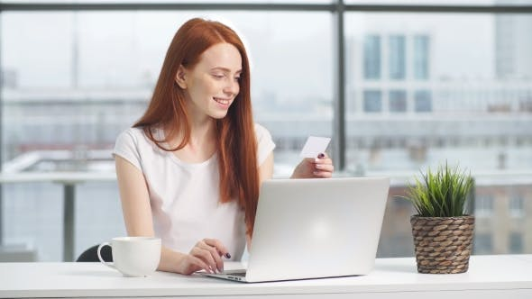 Thumbnail for Happy Redhead Girl Shopping Online with Credit Card and Laptop.
