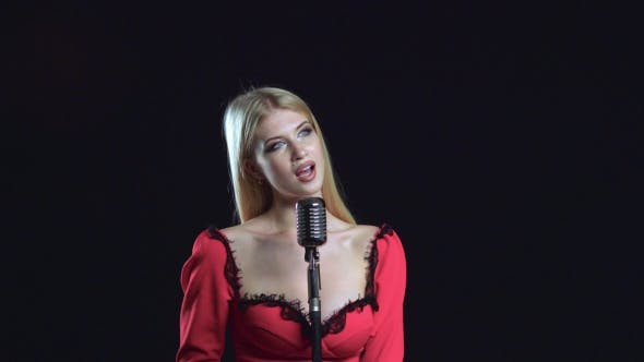 Thumbnail for Girl Sings in a Soft Voice in a Retro Microphone. Black Background
