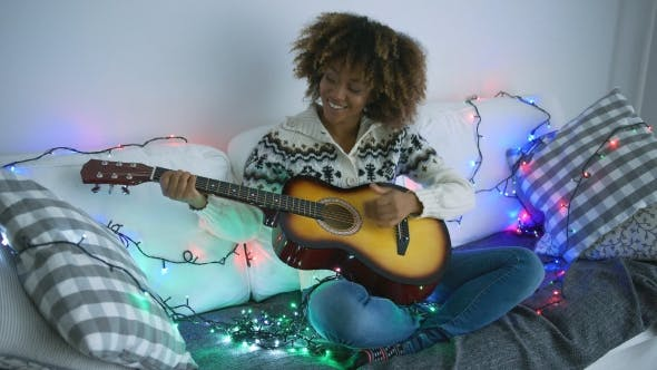 Thumbnail for Cheerful Woman Playing Guitar in Garland Lights