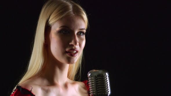 Thumbnail for Girl Dances and Sings in a Retro Microphone. Black Background. . Side View