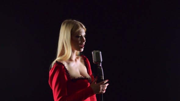 Thumbnail for Singer Is Sexy and Gentle Sings in a Retro Microphone. Black Background. Side View